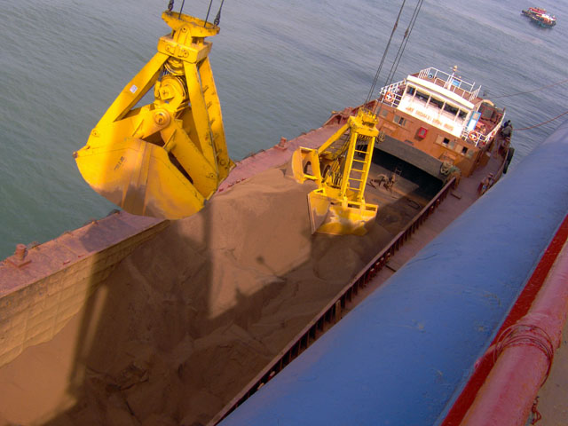 Goan Pride's cranes transferring iron ore from barges