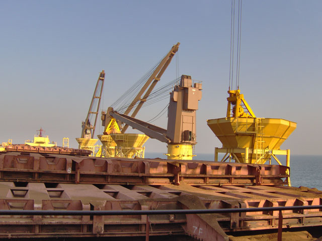 Goan Pride's cranes transferring iron ore from barges to deck hoppers for direct hit to OGV